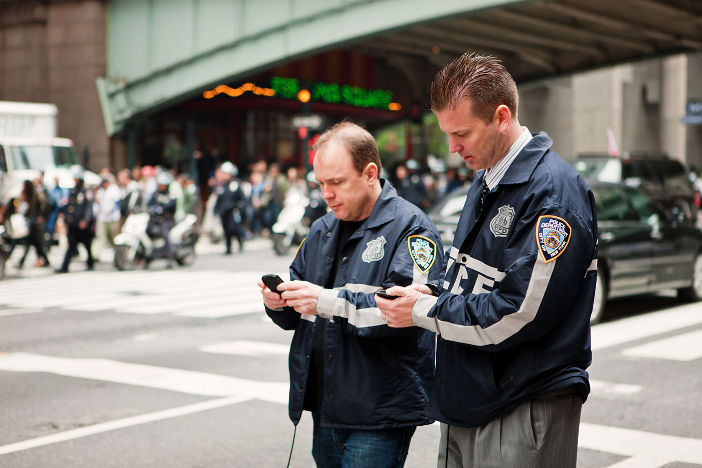 Two policemen on 42nd street using their mobile phone.